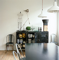 An early 20th-century metal cupboard in this contemporary dining room houses antique and decorative ceramics