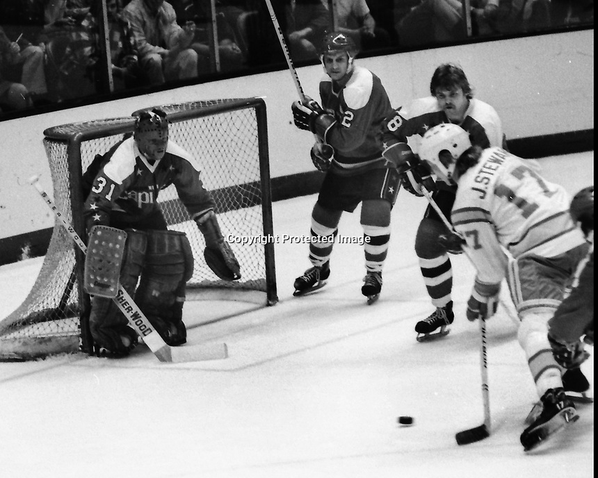 Seals John Stewart closes in on Washington Capitols goalie Michel Belhumeur, #2 Jack Lynch, and #8 Don McLean. (1975 photo by Ron Riesterer)