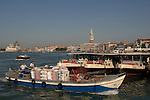 Transporting goods on a river barge, passing docked water buses and the skyline of Venice.