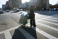 A bottle collector with a shopping cart full of recyclables on his way to redeem them is seen in the New York neighborhood of Chelsea on Wednesday, march 28, 2012.  (© Richard B. Levine)
