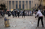 A protester throws a rock at police, Cairo, Egypt, Friday, Jan. 28, 2011. Tens of thousands of people took to the streets after Friday prayers, demanding that President Hosni Mubarak step down. Demonstrators clashed with police throughout the day and night as they marched toward Tahrir Square.