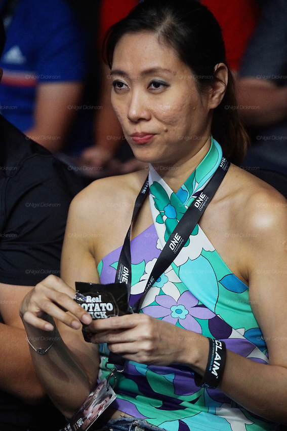A woman eats potato snacks. Spectators watch the MMA cage fighting<br />
