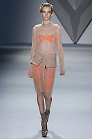 Daria Strokous walks runway in a nude net lace long sleeve dress with melton epaulettes and high neck collar over tangerine melton bra with nude melton zip-front peplum, and tangerine techno stretch bermuda short, from the Vera Wang Fall 2012 Vis-a-gris collection, during Mercedes-Benz Fashion Week Fall 2012 in New York.