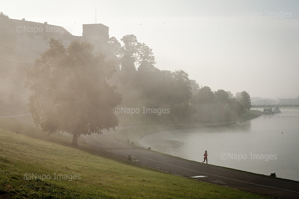 KRAKOW, POLAND, SEPTEMBER 13, 2011:.Lone runner is jogging early morning along the banks of Vistula river near Wawel hill royal castle. .(Photo by Piotr Malecki / Napo Images) ..KRAKOW, 9/2011:.Wawel i Wisla o poranku. .Fot: Piotr Malecki / Napo Images