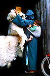 Woman dressed in traditional arab dress carrying her child on her back. She is holding sheepskins in her hand.  Cassablanca,Morocco. 1975