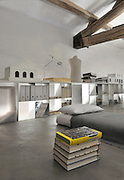 A functional, light industrial style space with exposed roof beams and a concrete floor. A single mattress sits on the floor with a grey cover. A storage unit runs along the length of one wall.