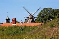 Man running past historical windmill in Copenhagen, Denmark.