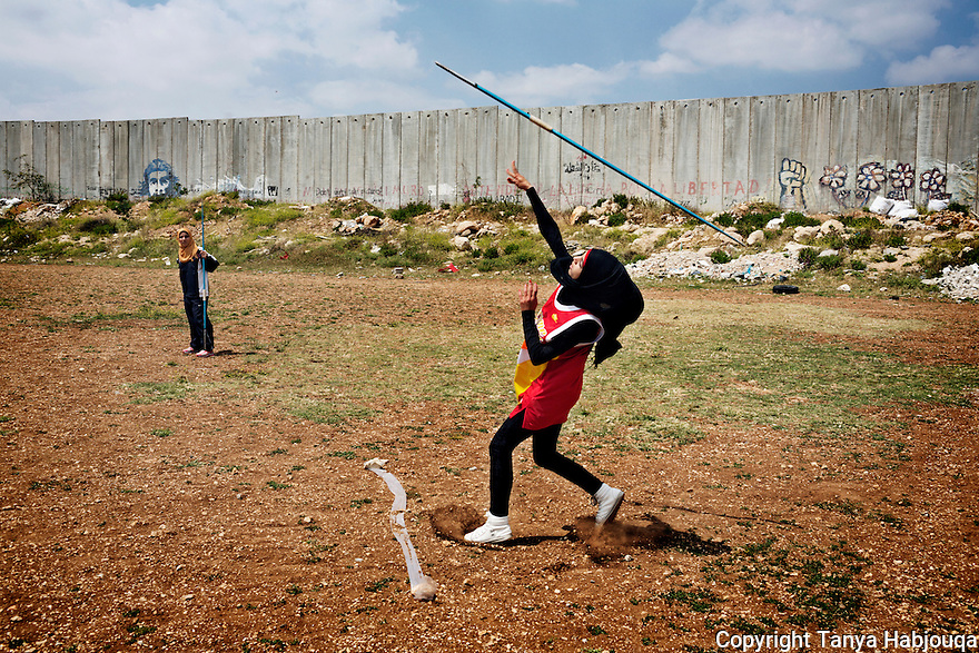 West Bank: Students  from the Al-Quds University javelin team wrap up the last practice before summer vacation in the West Bank city of Abu Dis, next to the Israeli Separation Wall. 2013