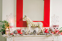 A model horse takes centre stage amidst the baubles and pine cones that decorate the mantelpiece in the living room