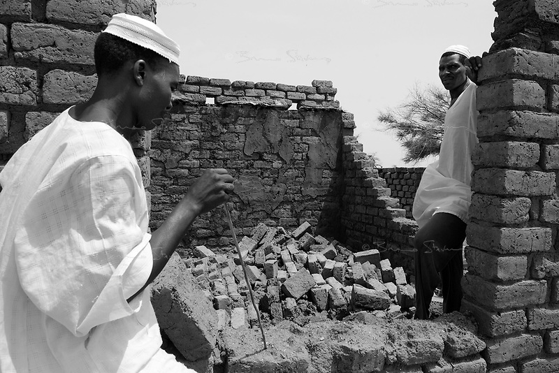 Sani Daleba, South Darfur, August 1, 2004.Baker Suleman Juma (R) in the ruins of his home with a friend, Mussa Ismael (L). Protected by a small police force, a few hundred 'Fur' farmers have begun returning to their small town, completely destroyed two months ago by Janjaweed attacks.
