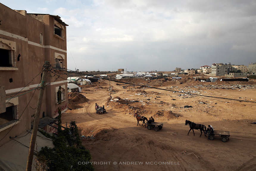 Horses and carts approach the tunnels at Rafah, in southern Gaza. The white tents in the background each represent a single tunnel and the border with Egypt can be seen on the left.