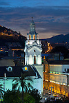 The illuminated bell tower of the 16th century Iglesia de San Agustin in Old Town Quito stands in contrast to the modern hillside buildings on Itchimbia hill.  On top on the hill the sits a park and a glass structure known as the Centro Cultural Itchimbia.