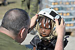 A Canadian military police helps a Haitian girl put on a helmet before being evacuated by helicopter from Jacmel, on the earthquake-ravaged country's southern coast.