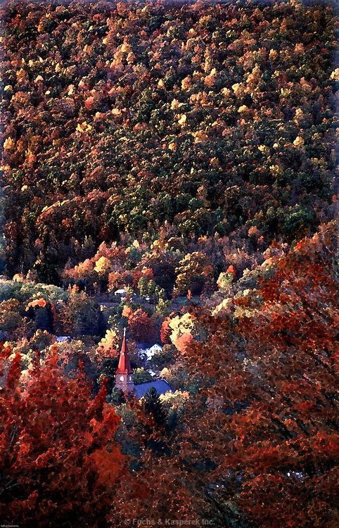 A church steeple rises through the Autumn colors in Salamanca, New York.