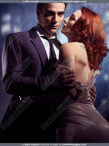 Sensual portrait of a couple standing in front of a window on a rainy night. Man in suit taking off young red-haired woman dress.