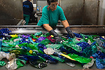 "An employee sorts plastic waste collected in the sea by fishermen at a plastic processing plant in Chiva, near Valencia on November 3, 2015. Ecoalf, a Spanish Madrid-based firm founded in 2010, has already launched ""a new generation"" of clothes and accessories made from plastic bottles, old fishing nets and used tires found on land. © Pedro ARMESTRE"