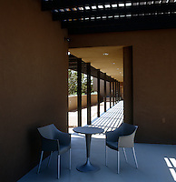 This contemporary style adobe property has a shady wrap-around terrace