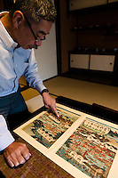 """Tokubee Masuda, CEO of the Tsukinokatsura sake brewery. He is looking at a woodblock print showing sake brewing in Fushimi during the Edo Period. Fushimi, Kyoto, Japan, October 10, 2015. Tsukinokatsura Sake Brewery was founded in 1675 and has been run by 14 generations of the Masuda family. Based in the famous sake brewing region of Fushimi, Kyoto, it has a claim to be the first sake brewery ever to produce """"nigori"""" cloudy sake. It also brews and sells the oldest """"koshu"""" matured sake in Japan."""