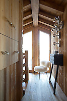 A sheepskin-covered chair is the focus of this chalet landing, with wood-clad walls lined with built-in drawers opposite a series of silver-topped lightbulbs as a lighting feature with a difference