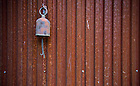 Aug, 23, 2013; A cow bell hangs outside the front door of a home in Tryon Farm in Michigan City, IN. Photo by Barbara Johnston/University of Notre Dame