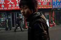 Shoppers and workers walk through a mostly Han wholesale market in Urumqi, Xinjiang, China.  The city is a major point on the so-called New Silk Road transportation network funneling goods between  China and Central Asia and beyond. The city is divided between Han and Uighur ethnic groups and in 2009 saw violent clashes between the groups.