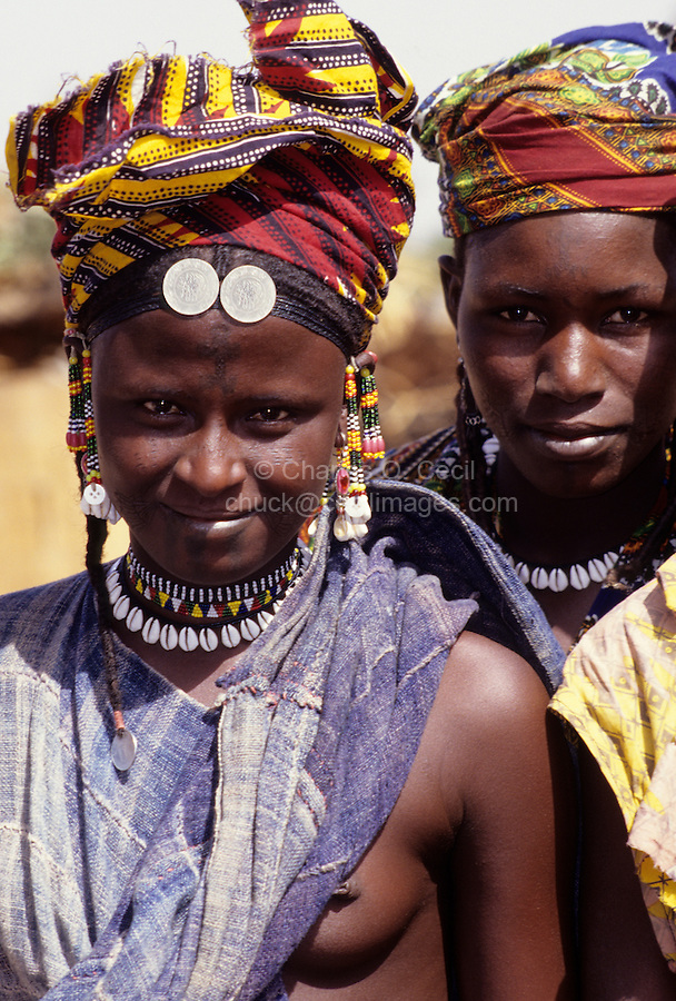Delaquara, Niger. Two Fulani Women.  Earrings, Cowrie Shell Necklaces, Headscarves.  Saudi Arabian coins fixed to the headscarf indicate that someone in the village, probably the lady's husband, has made the pilgrimage to Mecca.