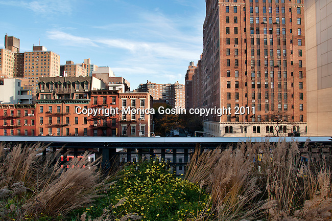 A view of the buildings, street, and Chelsea neighborhood below the Highline, a public park on an old elevated railway track in New York City