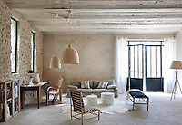 The spacious living room where a large cow-hide rug softens the concrete floor and the bespoke metal windows and doors are the work of local craftsman Jules Teras