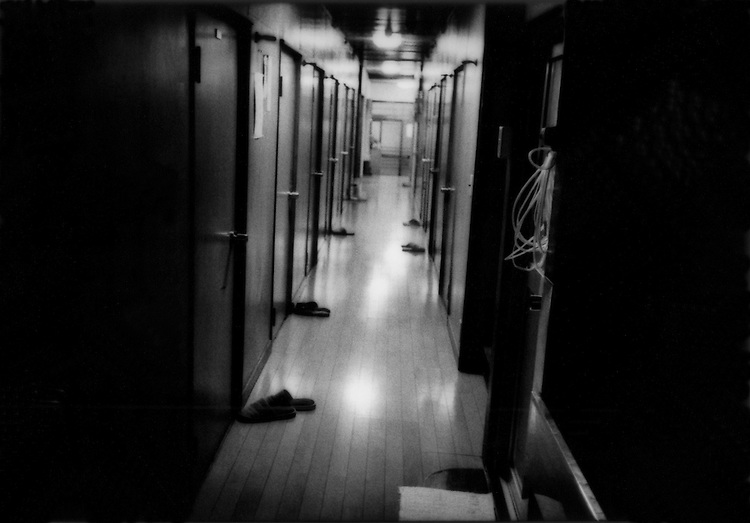 Interior hall of a do-ya with men's slippers left outside the tatami mat rooms, Sanya, Tokyo, Japan.  Do-ya are the lowest level of boarding house inhabited by day labourers and other men who cannot afford the deposits for an apartment.