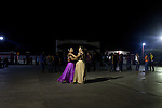"""Two women dance during a party in the town of San Mateo...The Isthmus of Tehuantapec, long a center for indigenous land ownership, is now embroiled in a land dispute over wind farm land...Called """"Mexico's little waist,"""" the Isthmus is a wind tunnel that links the Gulf of Mexico to the Pacific through mountain passes at the narrowest part of Mexico. The geographical funnel makes it one of the windiest places in North America and for a decade wind energy companies have been jostling to acquire land to power the likes of Coca-Cola and Wal Mart."""