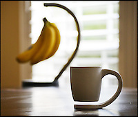 BNPS.co.uk (01202 558833)<br /> Pic: BNPS<br /> <br /> A modern mug which promises to rid furniture of coffee rings once and for all has the humble banana to thank for its clever design.<br /> <br /> Pals Dumi Ndlovu and Tigere Chiriga dreamed up the Floating Mug - which comes with its own built in coaster - after spotting bananas hanging on a hook.<br /> <br /> The pair say it will revolutionise the way tea and coffee drinkers think about mugs - and expect one to be in every home soon.<br /> <br /> Unlike other mugs, the Floating Mug's handle bends round underneath it to form a coaster to collect any drips that could form stains on tables and worktops.<br /> <br /> The Floating Mug is available from the compay's online shop for &pound;22.<br /> <br /> It is the product of months of hard work by financial analyst Dumi and post office worker Tigere, both 34, who grew up together in Harare, Zimbabwe.<br /> <br /> Dumi, who now lives in Reading, UK, said: &quot;A few years ago the idea for the floating mug was born.