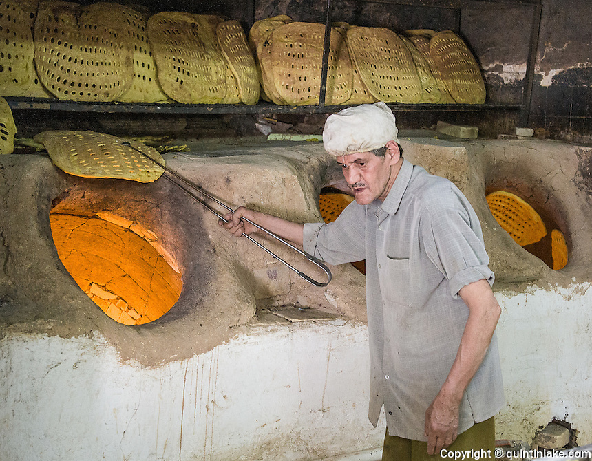 Baker taking bread out of his tandoor oven at his bakery in Yazd, Iran