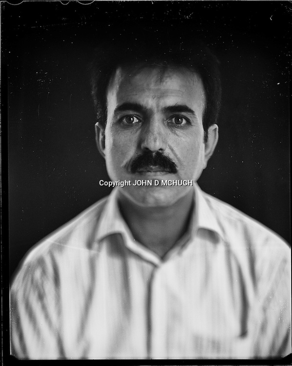 """Abdul Waheed Khalili, Director of the Turquoise Mountain Foundation, is seen in his office in Kabul, 26 August 2012. This portrait was shot on a 5x4 Linhof Technika IV, circa 1959, and a Schneider Kreuznach 270mm lens, circa 1952, with front tilt, and is part of a series entitled """"Putting an Afghan face on the war."""" (John D McHugh)"""