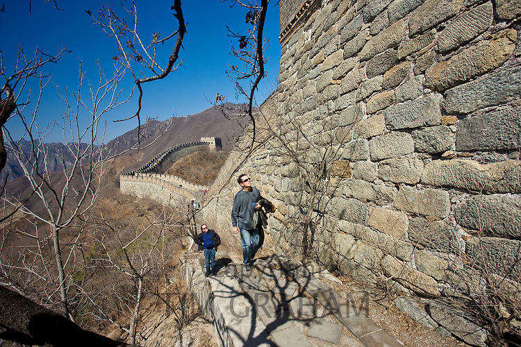 Two men walk along the side of the Great Wall of China at Mutianyu, north of Beijing (formerly Peking), China