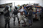 © Remi OCHLIK/IP3 - Port au Prince on 2010 december 10 - PORT-AU-PRINCE -- Haitians prepared for more violence Friday as rival candidates told supporters to take to streets and tip the balance in a sharply disputed presidential election stained by claims of fraud. Barricades were cleared overnight, but new flaming piles of tires were set up in parts of the city to block off traffic. People rushed to stores opening for the first time in three days to get food, water and provisions for fear the riots will heat up again. Haitian policemen patrol around Cite Soleil and aviation refugees camp, controlling people lookong for weapons.