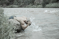 shirtless man cooling off in a river in New Mexico