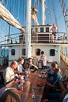 Ireland, July 2013. Dinner on deck. It is the first time that Tallship Thalassa, a barquentine sailing vessel with 3 masts, sails from Belfast to Galway along the Irish coastline. While a full-rigged ship is square-rigged on all three masts, and the barque is square-rigged on the foremast and main, the barquentine extends the principle by making only the foremast square-rigged. The advantages of a smaller crew, good performance before the wind and the ability to sail relatively close to the wind while carrying plenty of cargo made it a popular rig at the end of the 19th century. Photo by Frits Meyst/Adventure4ver.com