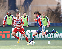 New England Revolution forward Juan Toja (7) dribbles as FC Dallas midfielder Michel Garbini (31) defends..  In a Major League Soccer (MLS) match, FC Dallas (red) defeated the New England Revolution (blue), 1-0, at Gillette Stadium on March 30, 2013.