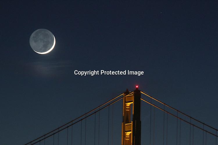 The crescent moon setting behind Golden Gate Bridge as seen from Marina Greens, San Francisco, CA.