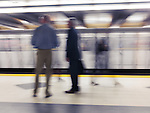 People standing on a subway platform waiting for a train. Artistic motion blur. Toronto, Ontario, Canada.