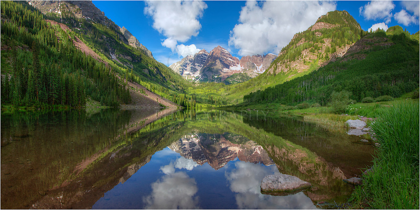 After an early morning of landscape photography at Crater Lake under the shadow of the iconic Maroon Bells, I made my way back down Maroon Creek, eventually ending up where everone takes their pictures of the lake and both Maroon and North Maroon Peaks in the distance. And I had to take part, too, especially because skies were just about perfect for a summer morning, and the reflections were like glass.<br /> <br /> This Maroon Bells Panorama was made from two images stitched together. I wanted to show the width of the landscape in this photograph. I loved the colors I witness, and also wanted to convey that to my audience, as well.