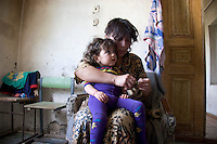 A woman puts on her daughter's shoes in Nachichevanik, Nagorno-Karabakh.