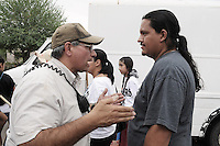 """Phoenix, Arizona (July 28, 2012) - About three hundred people marched to protest the second anniversary of the approval of some provisions of the SB 1070 immigration law. The march, called """"No Papers, No Fear"""" was organized by immigrant rights groups who say the law discriminates people of brown skin. In this photograph, Phoenix Police Detective Al Ramirez (left) talks to Carlos Garcia (right), Puente Movement Director and organizer before the """"No Papers No Fear"""" march begins at the Steele Indian Park in Phoenix. The march was held to oppose Arizona immigration law SB 1070 and racial profiling. Photo by Eduardo Barraza © 2012"""