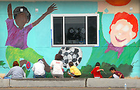 Teachers, parents, and students help paint Artist David Legaspi's multicultural -themed mural at Franklin Elementary School on Sunday, October 23, 2011