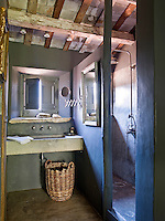 The rustic bathroom has a polished concrete floor, untreated concrete basin and large rain shower