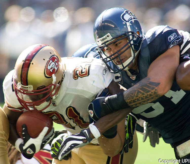 San Francisco 49ers running back Frank Gore, left, runs for short yardage before being tackled by Seattle Seahawks linebacker Lofa Tatupu in the first quarter at Qwest Field in Seattle on Sept 14, 2008. (UPI Photo/Jim Bryant).