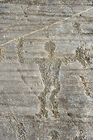 Petroglyph, rock carving, of a warrior with a shiled. Carved by the ancient Camuni people in the iron age between 1000-1600 BC. Rock no 24,  Foppi di Nadro, Riserva Naturale Incisioni Rupestri di Ceto, Cimbergo e Paspardo, Capo di Ponti, Valcamonica (Val Camonica), Lombardy plain, Italy