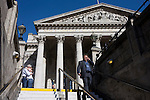 As a couple embrace, a commuter descends the steps from the bright daylight to the dark of the London Underground, before making his way home from Royal Exchange at Bank Triangle by tube. Behind him are the tall and solid Corinthian pillars of the 3rd Royal Exchange built in 1842 by Sir William Tite.
