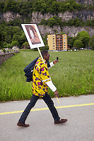 Switzerland. Canton Valais. St-Maurice. Africa Saints Pilgrimage (P&egrave;lerinage aux Saints d'Afrique). Religious <br /> procession. An african man carries a religious drawing and takes pictures with his mobile phone while walking on a road towards St-Maurice's abbey.  2.06.13 &copy; 2013 Didier Ruef