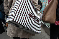 A shopper carries her Henri Bendel purchases on Fifth Avenue in New York during the Christmas shopping season on Saturday, December 1, 2012. (© Richard B. Levine)
